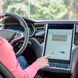 Woman using graphical display in electric car