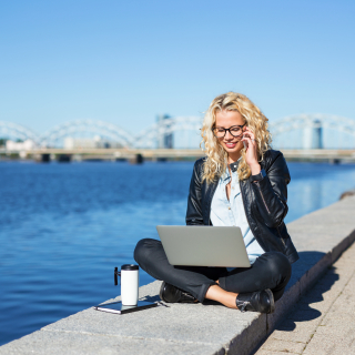 Woman with laptop and phone working outdoors