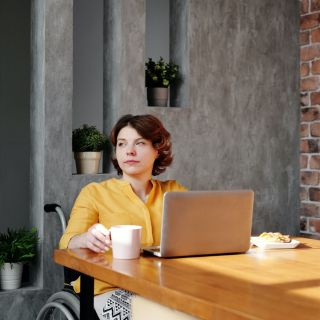 Women in a wheelchair with a computer in her home
